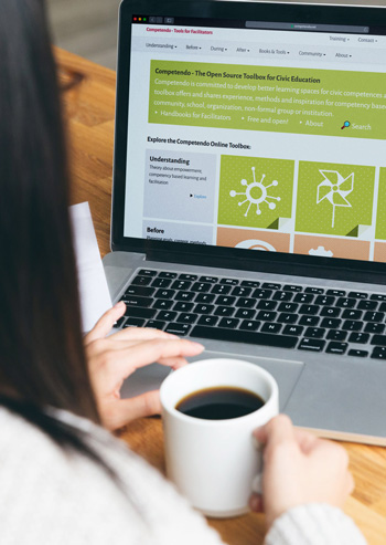 Mockup photo of woman sitting in front of a laptop with the Competendo website open