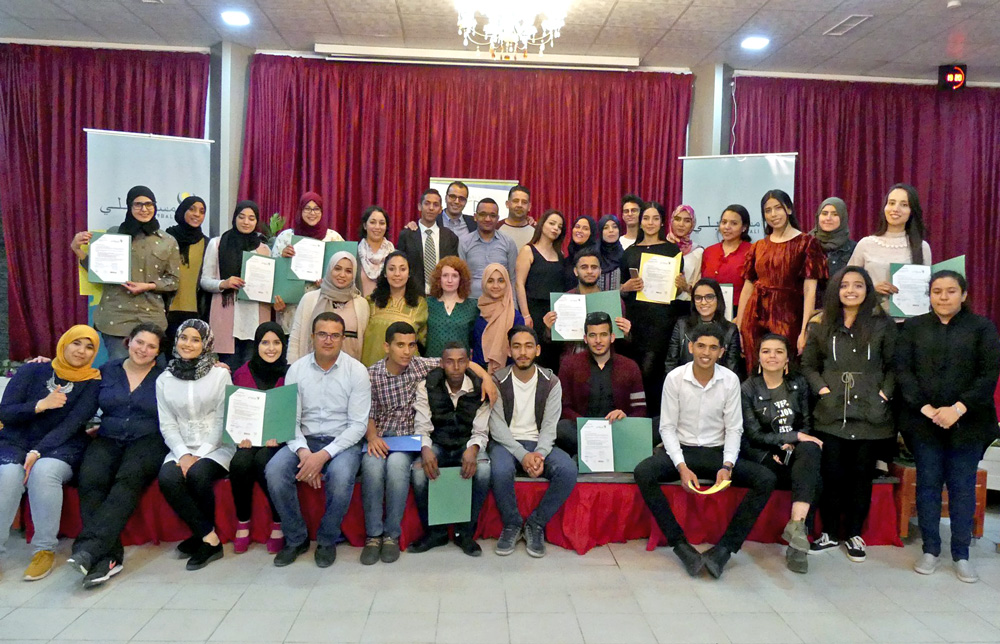 A group of about 40 young people, holding up certificates and smiling into the camera.